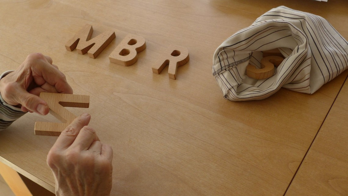 Demenz stock photo featuring wooden letters and two elderly hands